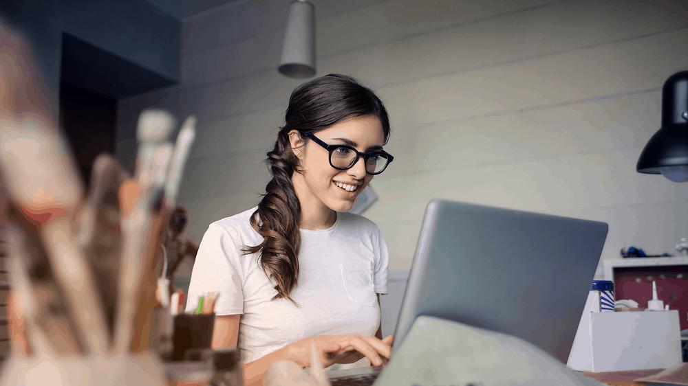 Woman looking at a computer smiling